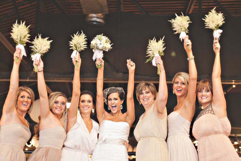 Bride and her bridesmaids and raise their bouquets