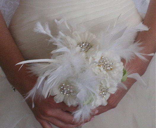 Bridesmaid bouquet of white silk flowers, rhinestone brooches and feathers with green ribbon accent