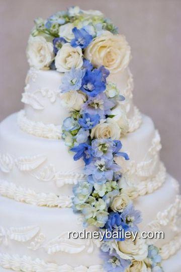Decor of cascading flowers on wedding cake.