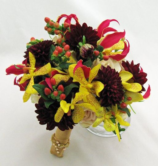 Lush colors of golds and burgundies. Flowers include gloriosa lilies, mokara orchids, and dahlias.
