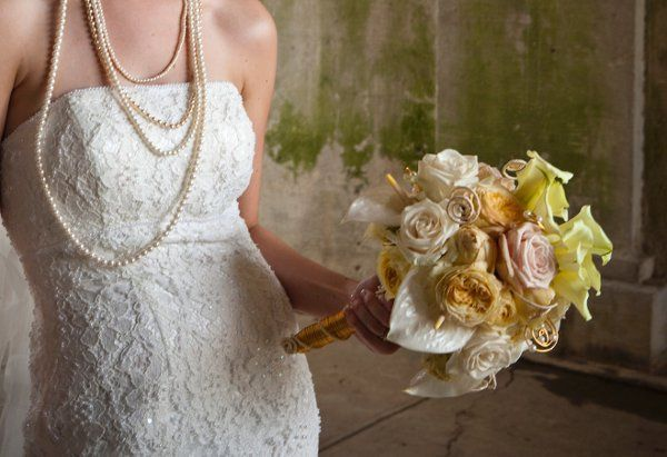 Bridal bouquet of anthuriums, calla lilies, garden roses, and ranunculus with handle made of gold...