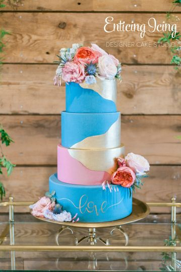 Gold dipped wedding cake with fresh floral and hand-painted calligraphy.