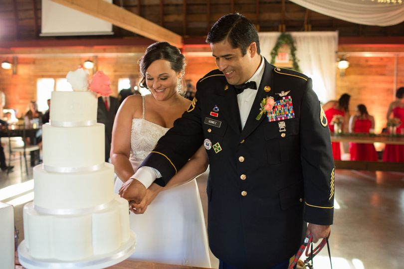 Bride and groom cutting their white wedding cake