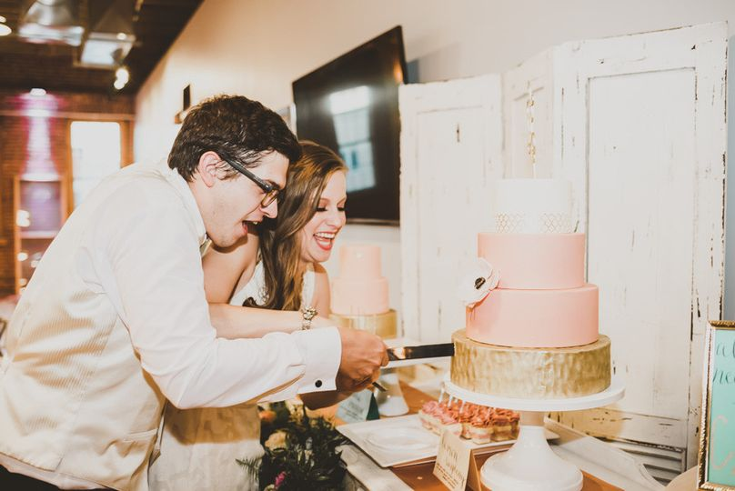 Bride and groom cutting their blush and gold wedding cake