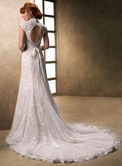 Carolina, A V-neckline and cap sleeve gown with Lace and Tulle finished with a ribbon belt.