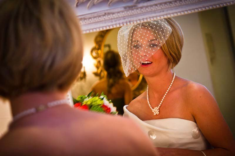 Bride getting ready with veil in mirror