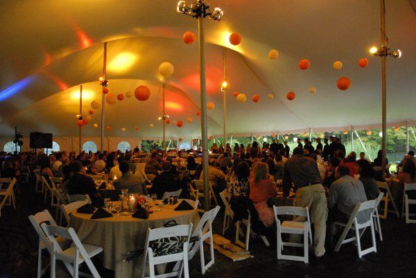 inside of a 60 wide twin peak tent with lights, chairs, tables, dance floor.