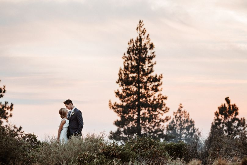 Newlyweds kiss by the woods