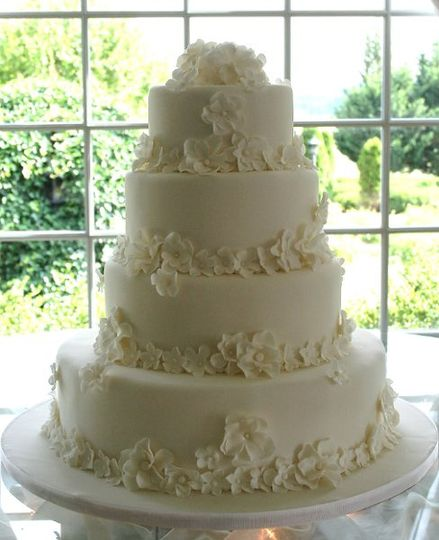 Flower drenched white on white four tier wedding cake. This cake is covered in over 100 handmade...
