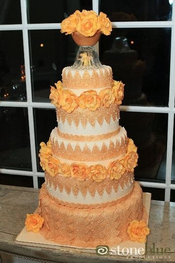 Handmade gold lacework sugar panels drape elegantly over the ivory covered tiers of this 5 tier...