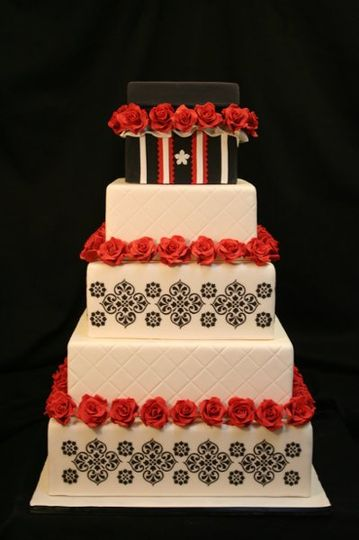 """Striking black white and red cake with crisp designs and handmade sugar flowers. Topped with a """"gift..."""