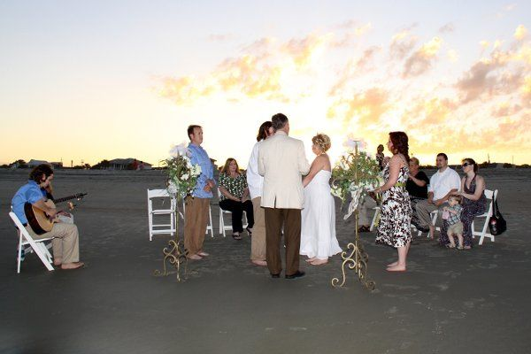 A ceremony at sunset on the Tybee Island beach with a barefoot guitar player.