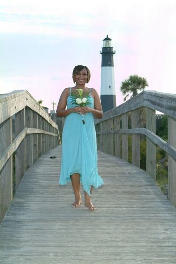 A bridesmaid walking in the processional to the beach ceremony site.