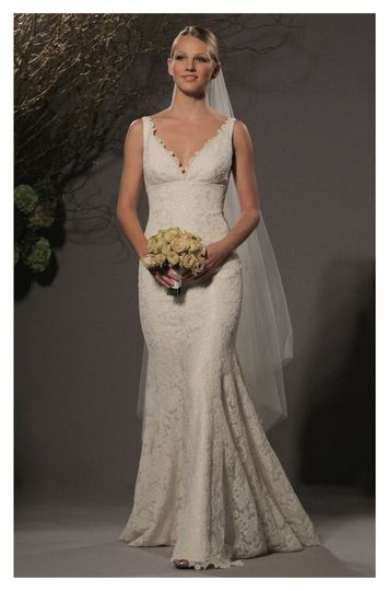 L237-V-neck gown made of re-embroidered lace, features a fitted bodice with a flowing fluted shaped...