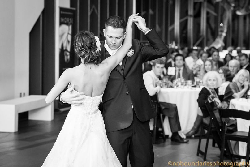 The couple embraces during their first dance as their guests enjoy the performance.