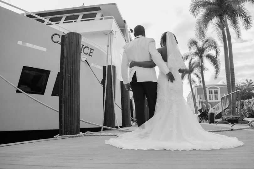 Bride and groom pose in front of boat