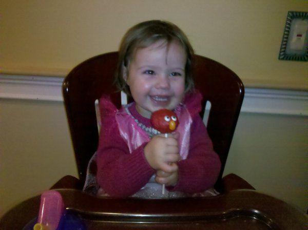 A very happy recipient of a vanilla Elmo cake pop!