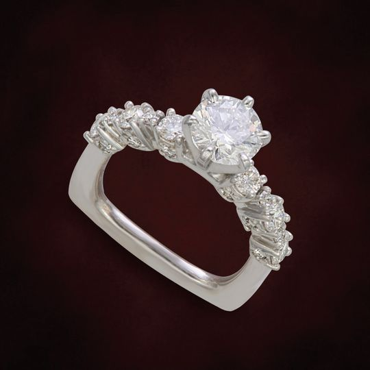 Large and small diamonds accent the top and fronts of this designer ring.  Prevents the rings from...
