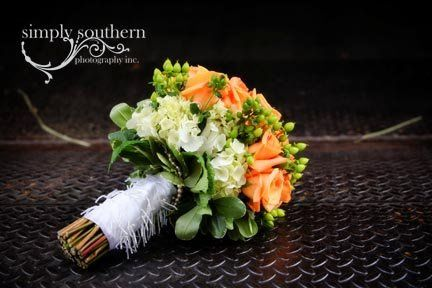 Modern orange bouquet with a wrap made from the bride's mother's wedding dress.