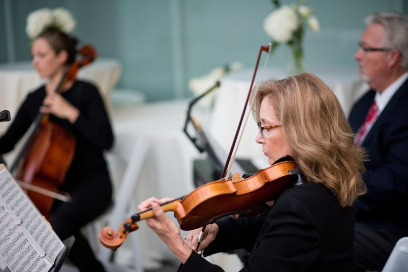 Vermilion strings' piano trio performing at an outdoor wedding