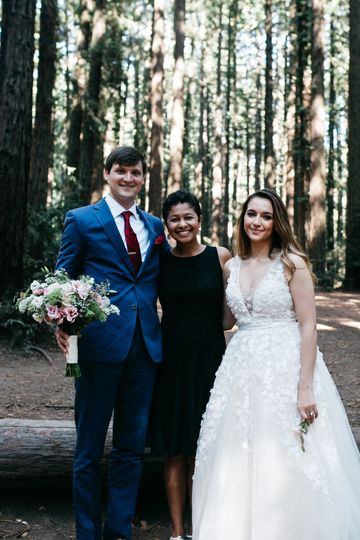 Newlyweds and officiant in the woods
