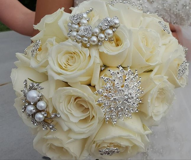 Cream roses with various types of brooches