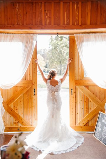 Bride looking out of barn.