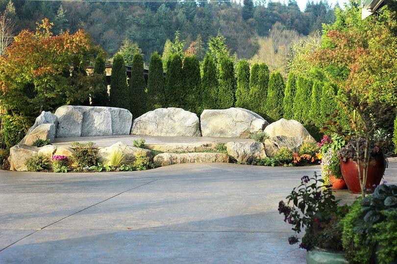 A beautiful natural granite rock stage is a focal point for ceremonies, with a large surrounding...
