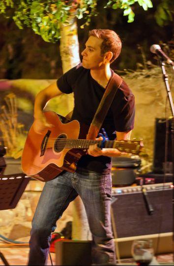 Aaron Goldfarb performing acoustic guitar at Ardivinos Desert Crossing
