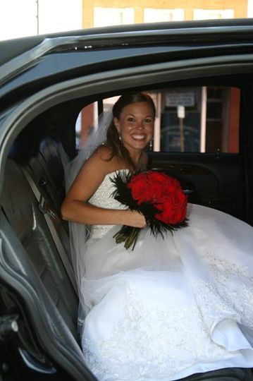 Bride in white wedding dress contrast with the black stretch limousine