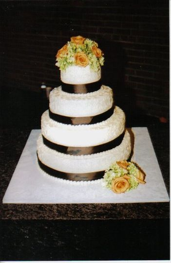 Different flavored layers with buttercream frosting, decorated with ribbon and fresh flowers