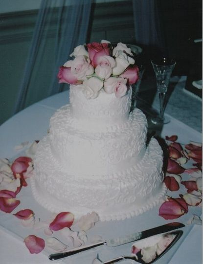 white cake with decorators frosting, decorated with fresh flowers
