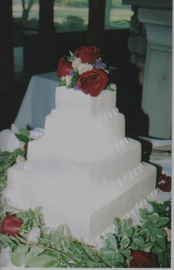 white cake with buttercream frosting, decorated with fresh flowers