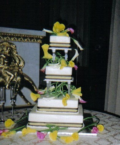 diffent flavored layers with buttercream frosting, decorated with ribbon and calla lillies