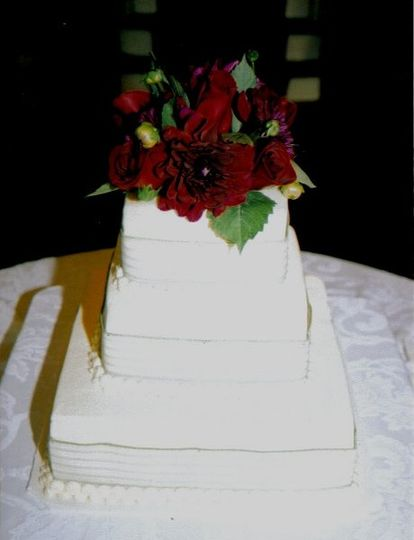 white cake with buttercream frosting, decorated with ribbon and fresh flowers