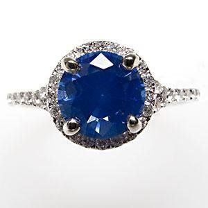 This magnificent natural blue sapphire engagement ring features a halo of diamonds surrounding the...