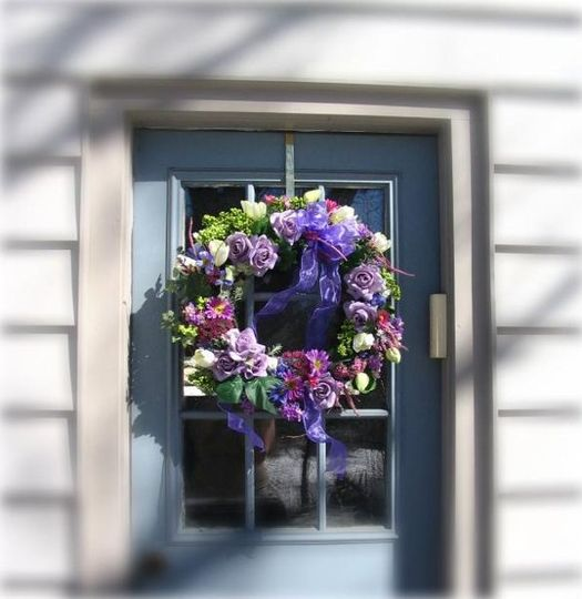 Silk wreath designed to coordinate with the wedding flowers will greet guests as they arrive and...