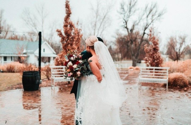 Bride holding bouquet by water
