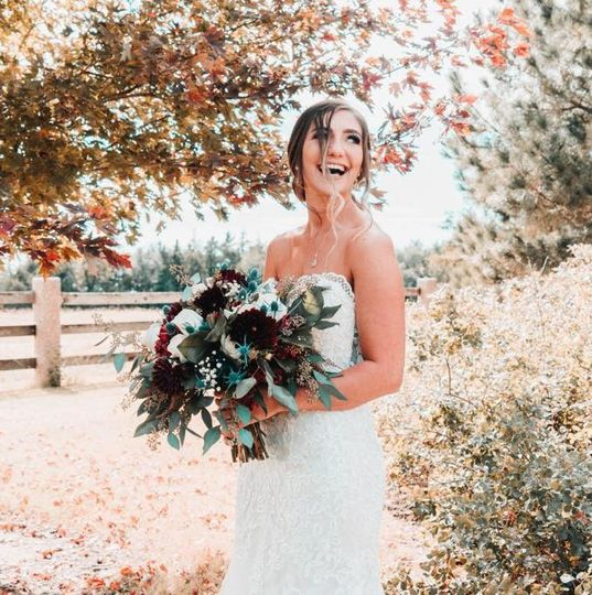 Bride standing under fall leaves