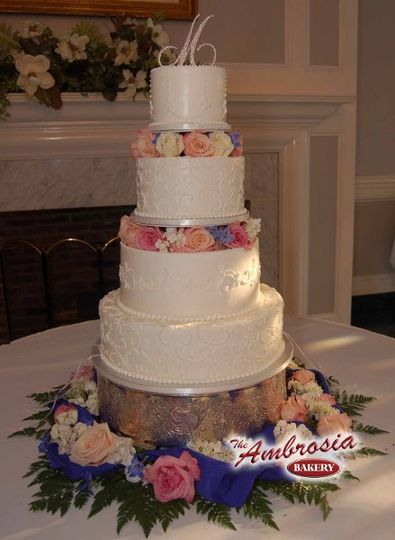 This buttercream cake has four tiers with two column breaks where the flowers are...
