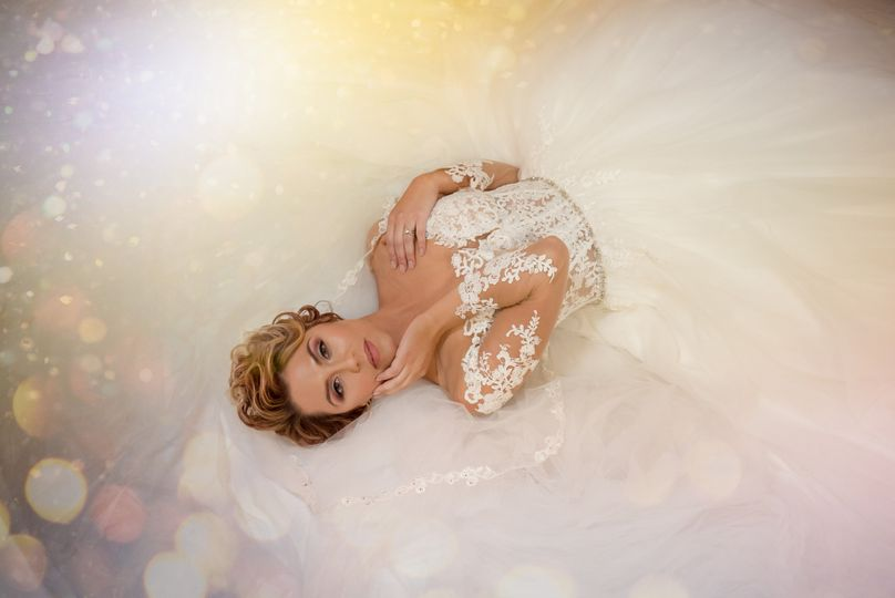 Bride lying down in her off-shoulder dress