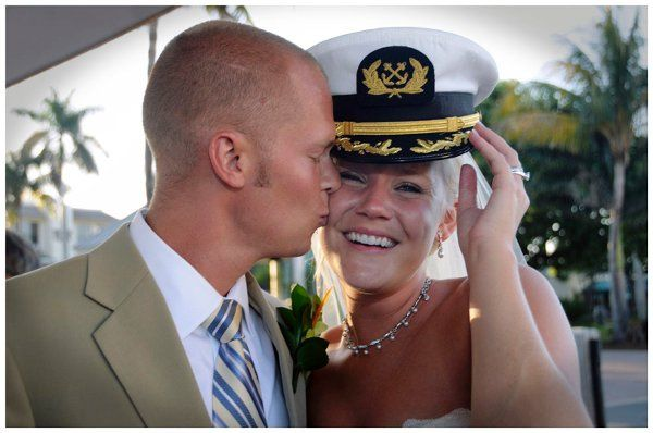 Groom kissing smiling bride wearing a captain's hat
