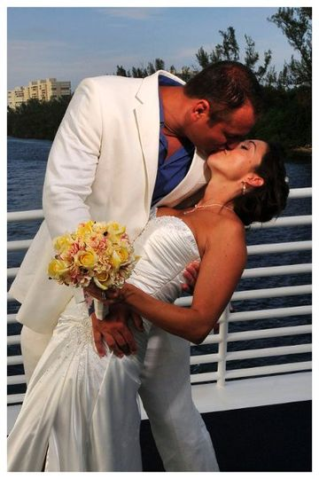 Groom dipping bride and kissing while aboard a beautiful yacht