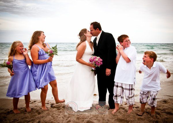 bride and groom kissing while children make silly faces at them, on the beach