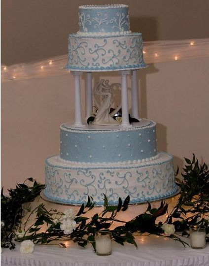 Light blue and white 4 tier cake with topper in the middle