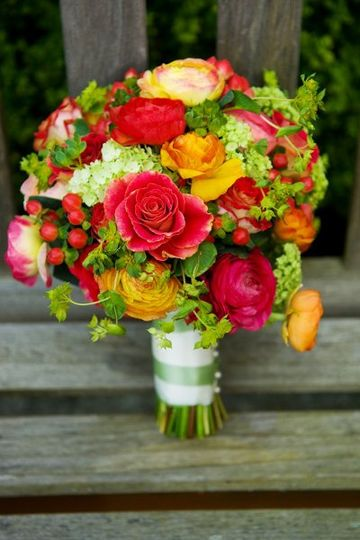 For Kristen's April wedding, we chose warm shades of ranunculus and paired them with lush green...