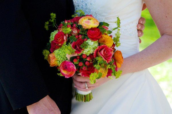 Kristen's early spring bouquet of warm shades of ranunculus, green viburnum, red hypericum berries,...