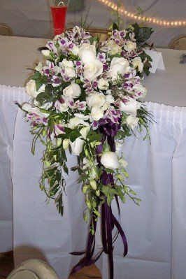 Bridal cascade of white roses, purple & white alstromeria, & white dendrobium orchids.