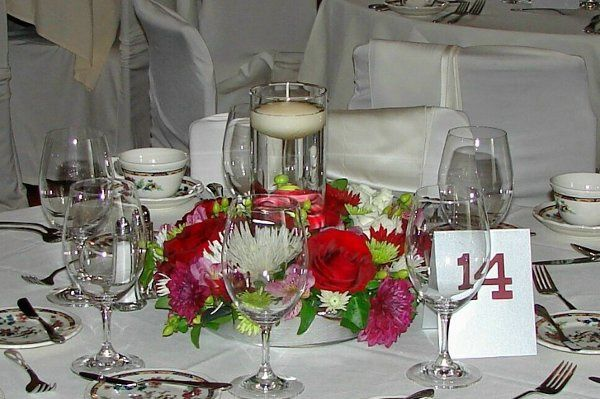 A ring of burgundy, ivory, & green blooms surround a cylinder filled with water & a floating candle.