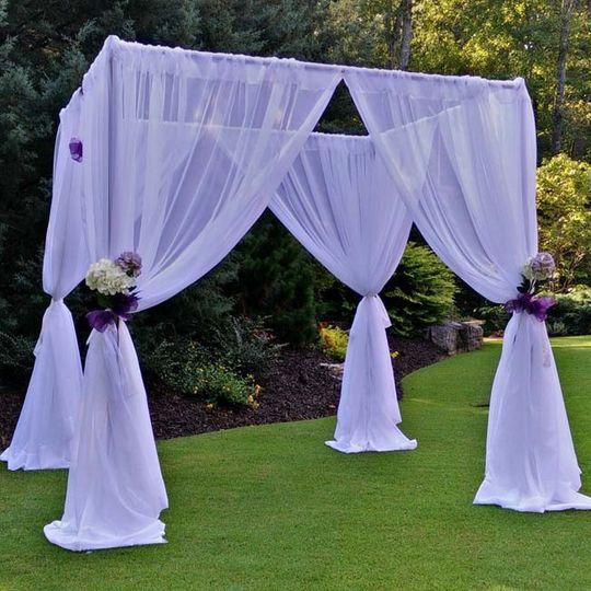 Chuppah with white drapes.
